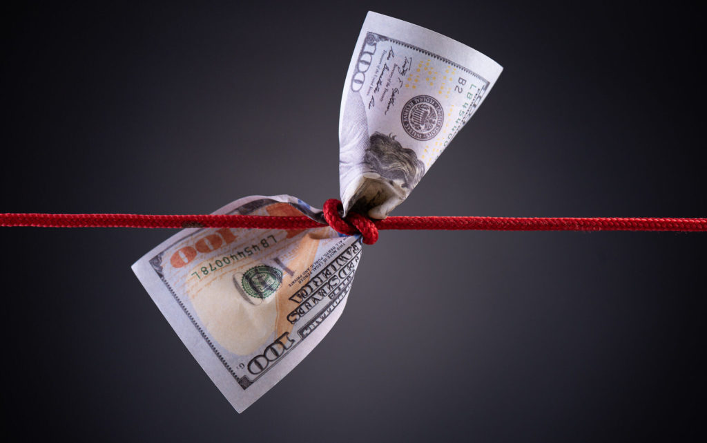 American dollar tied up in red rope knot on dark background with copy space. business finances, savings and bankruptcy concept.